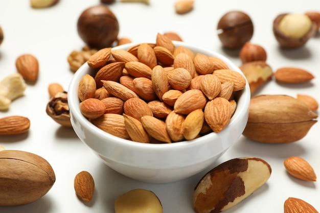 Kom met abrikozenzaden en verschillende noten op wit