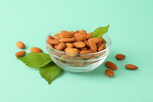 Kom met amandel op muntachtergrond. vitamine voedsel