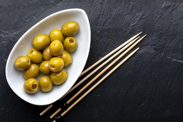 Kom met ansjovis gevulde olijven. op zwarte leisteen. schoolbord. tandenstoker. bovenaanzicht.