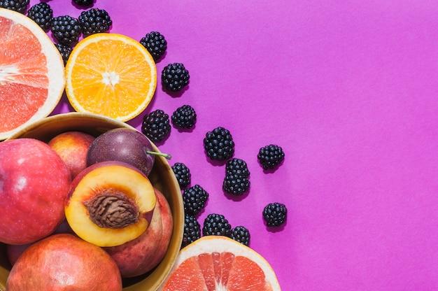 Kom met appel; perzik; oranje; druiven fruit plakjes en braambessen op paarse achtergrond