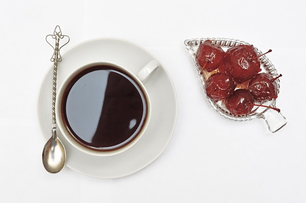 Kom met appeljam, dessert, een kopje met een drankje op een schotel en een zilveren lepel op een wit