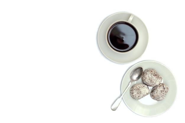 Kom met appeljam, dessert, een kopje met een drankje op een schotel en een zilveren lepel op een wit Premium Foto