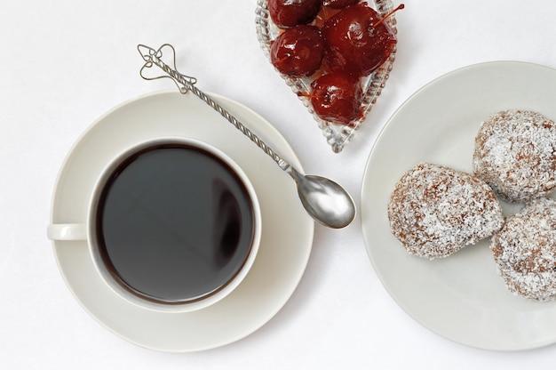 Kom met appeljam, dessert, een kopje met een drankje op een schotel en een zilveren lepel op een witte achtergrond.