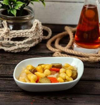 Kom met augurken op een houten tafel