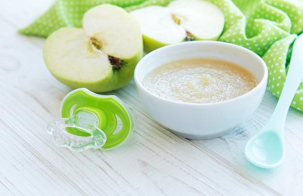 Kom met babyvoeding en appels op tafel