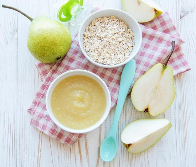 Kom met babyvoeding en peren op tafel