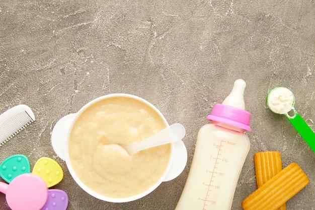 Kom met babyvoeding met speelgoed op grijze achtergrond