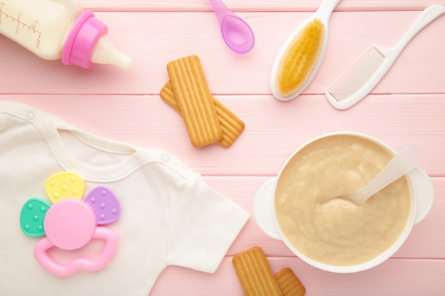 Kom met babyvoeding met speelgoed op roze tafel