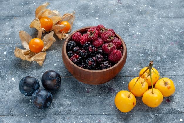 Kom met bessen vers en rijp fruit op grijs bureau, bessenfruit vers zacht bos