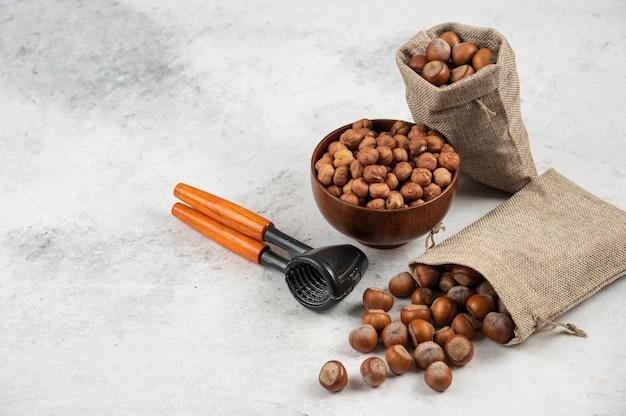 Kom met biologische hazelnootpitten en gepelde hazelnoten op marmeren tafel.