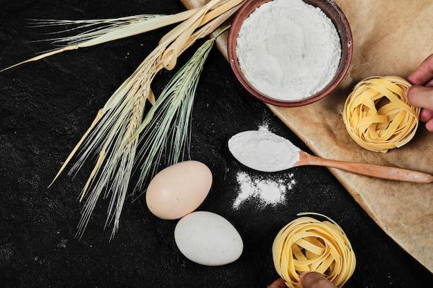 Kom met bloem, rauwe eieren, droge tagliatelle en houten lepel op donkere tafel.