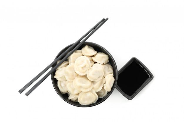Kom met bollen, eetstokjes en sojasaus die op wit wordt geïsoleerd