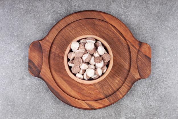 Kom met bruine snoepjes op een houten bord