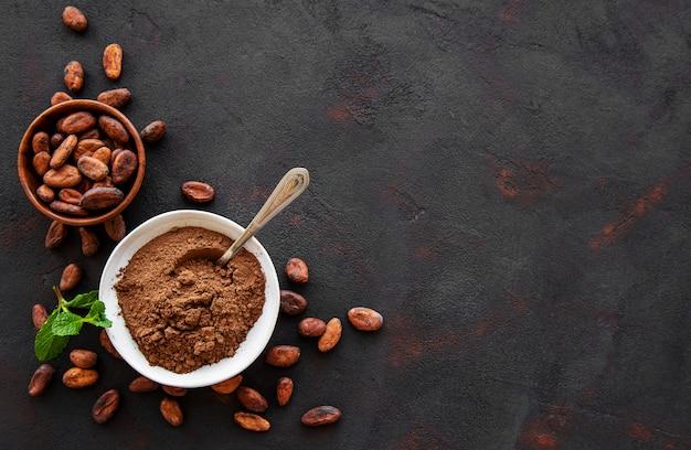 Kom met cacaopoeder en bonenachtergrond