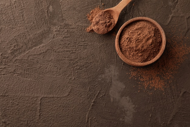 Kom met cacaopoeder en lepel op bruin, ruimte voor tekst