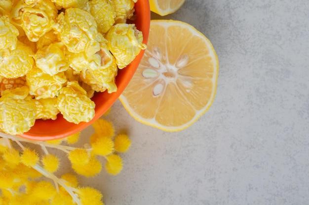 Kom met caramel gecoate popcorn, schijfje citroen en een bundel gezwollen bloemen op marmeren oppervlak