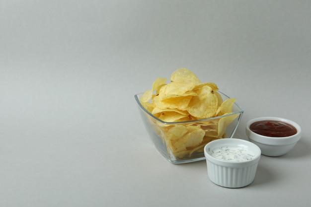 Kom met chips en sauzen op lichtgrijs oppervlak