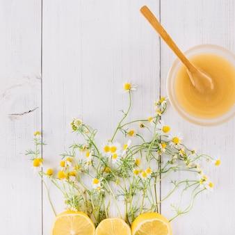 Kom met citroengestremde melk; kamille bloemen en citroen op houten plank