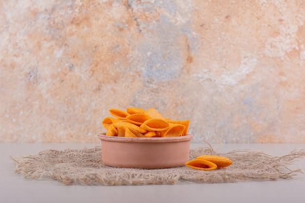 Kom met driehoekige knapperige chips die op marmeren achtergrond worden geplaatst. hoge kwaliteit foto