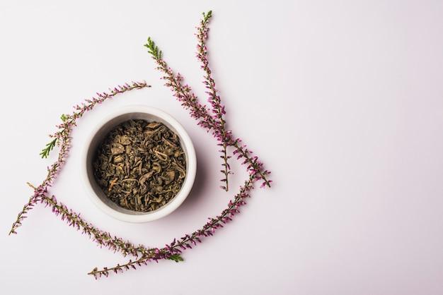 Kom met droge bloemblaadjes omringd met lavendel bloemen op witte achtergrond