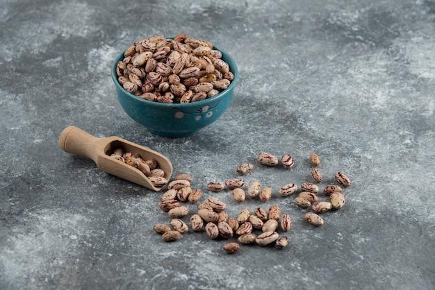 Kom met droge bonen en houten lepel op marmer.