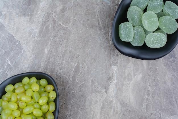 Kom met druiven en marmeladesuikergoed op steenachtergrond.
