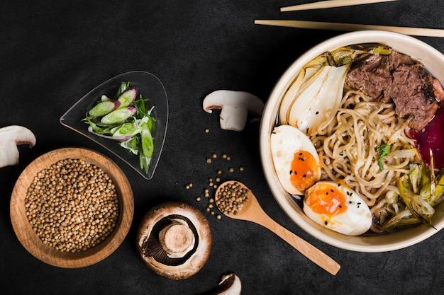 Kom met eieren; noedels varkensvlees met korianderzaad; paddestoel; bieslook en champignons op zwarte achtergrond