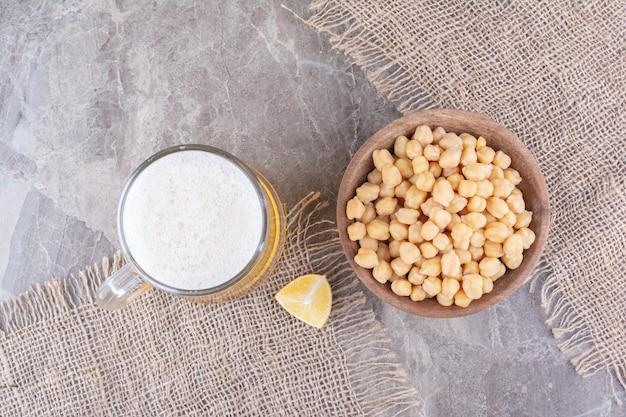 Kom met erwten en glas bier op marmeren oppervlak