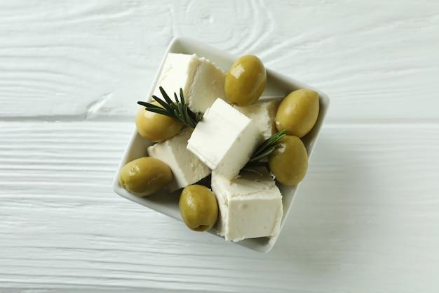 Kom met feta, olijven en rozemarijn op witte houten oppervlak
