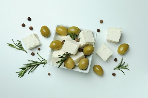 Kom met feta, olijven, rozemarijn en peper op witte ondergrond