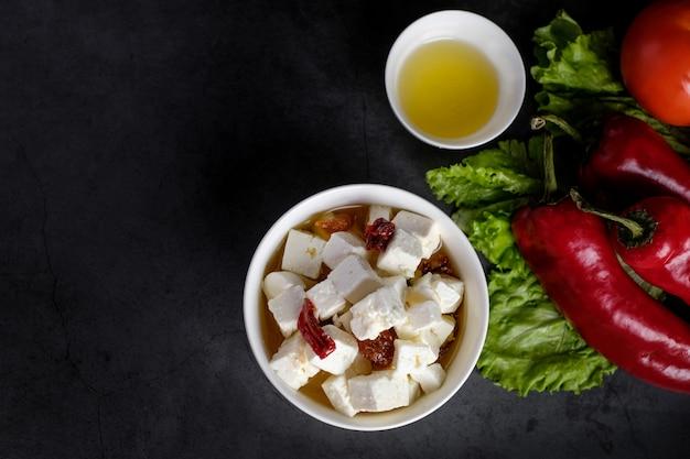 Kom met feta-stukken kaas en gedroogde tomaten en olie, bovenaanzicht met copyspace