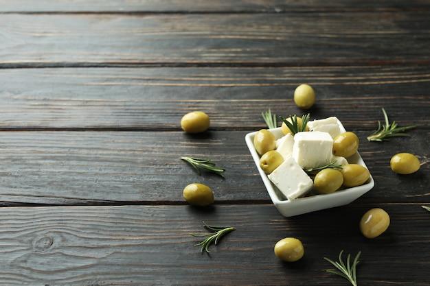 Kom met fetakaas, olijven en rozemarijn op houten oppervlak