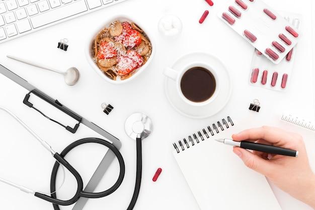 Kom met fruit voor het ontbijt en medische hulpmiddelen op bureau