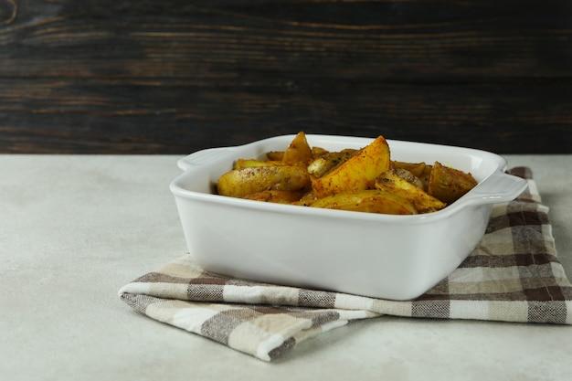 Kom met gebakken aardappel op keukendoek, op witte geweven lijst