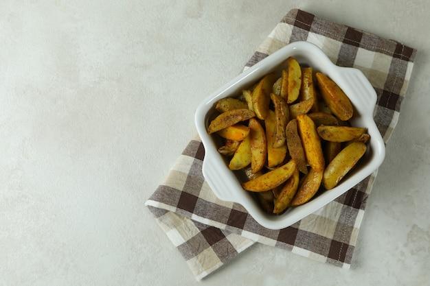 Kom met gebakken aardappel op keukenhanddoek, op witte gestructureerde achtergrond