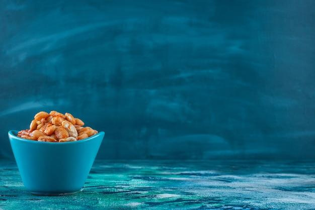 Kom met gebakken bonen, op de blauwe tafel.