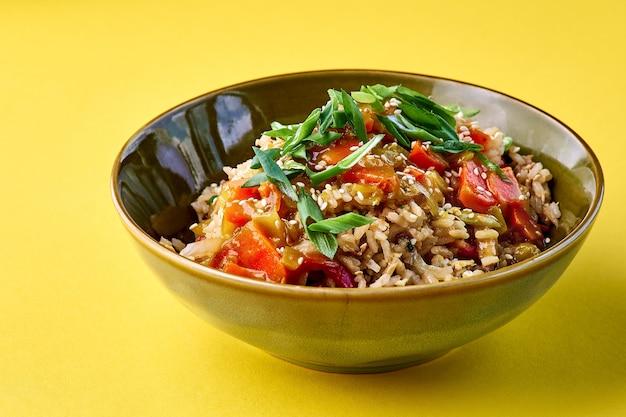 Kom met gebakken rijst en groenten. traditioneel chinees eten. horizontale weergave op geel