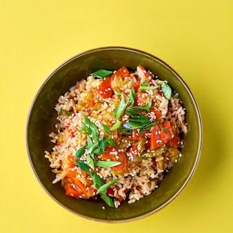 Kom met gebakken rijst en groenten. traditioneel chinees eten. vierkant zicht op geel. plat lag met kopie ruimte