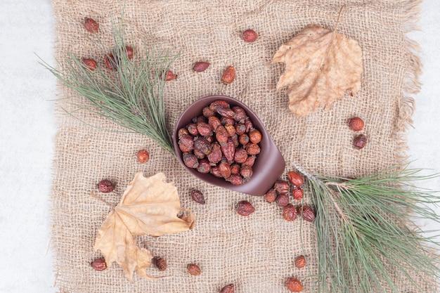 Kom met gedroogde amerikaanse veenbessen en blad op jute. hoge kwaliteit foto