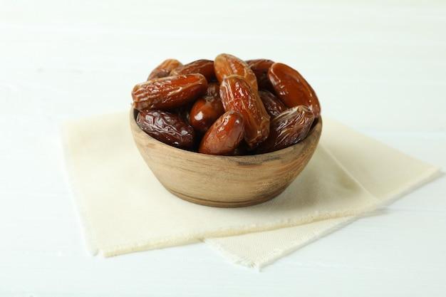Kom met gedroogde datums op keukenservet op witte houten tafel