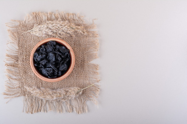 Kom met gedroogde pruimenvruchten die op witte achtergrond worden geplaatst. hoge kwaliteit foto