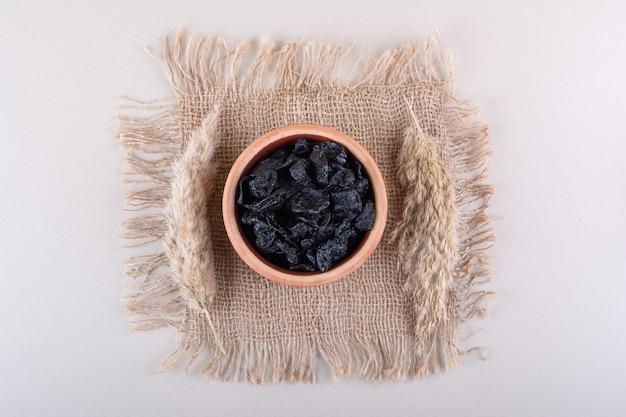 Kom met gedroogde pruimenvruchten geplaatst op een witte ondergrond. hoge kwaliteit foto