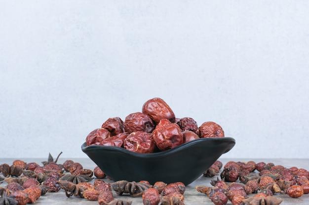 Kom met gedroogde rozebottels op stenen tafel.