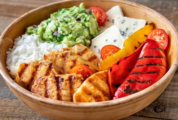 Kom met gegrilde kip, rijst, blauwe kaas en groenten