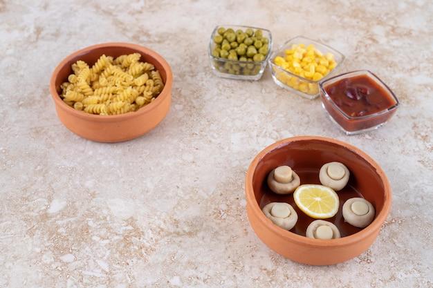 Kom met gekookte pasta en porties van verschillende toppings op marmeren oppervlak