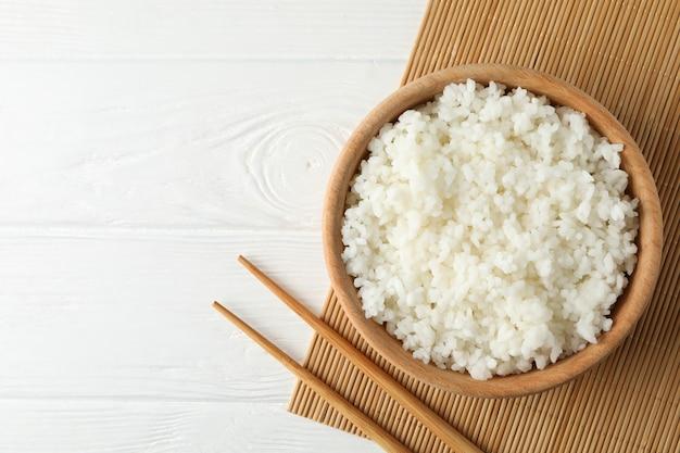 Kom met gekookte rijst en eetstokjes op houten oppervlak
