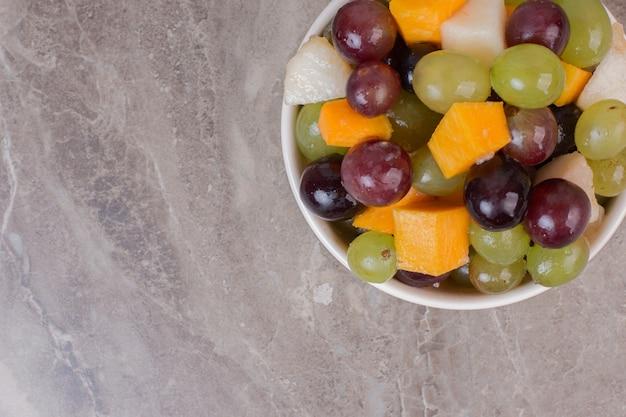 Kom met gemengd fruit op marmeren oppervlak.