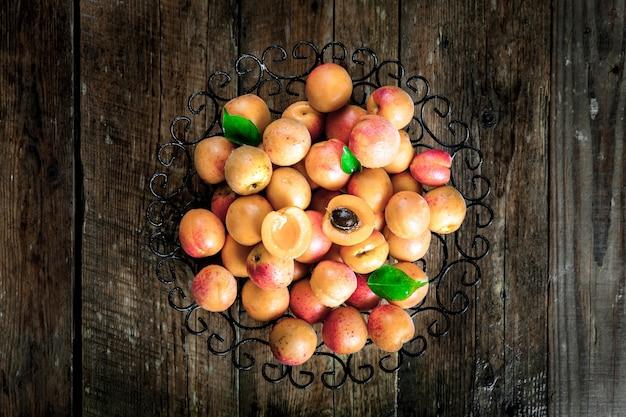 Kom met geoogste abrikozen. verse abrikozen op houten achtergrond