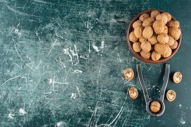 Kom met gepelde walnoten met het hulpmiddel voor het kraken van noten op marmeren tafel.