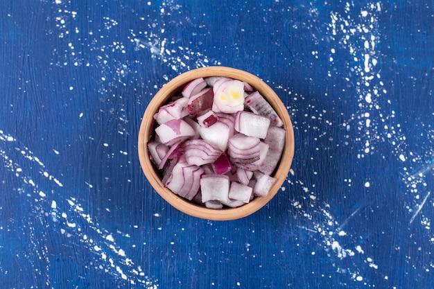 Kom met gesneden verse paarse uien op marmeren oppervlak